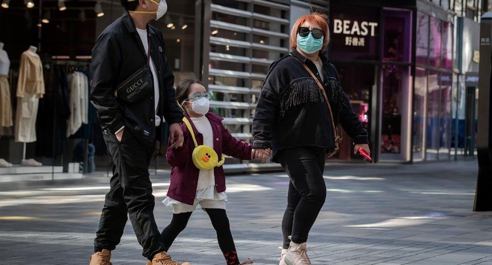 En esta imagen, tomada ayer, se aprecia a personas que usan mascarillas como medida preventiva contra el coronavirus caminando afuera de un centro comercial en Beijing. (AFP)