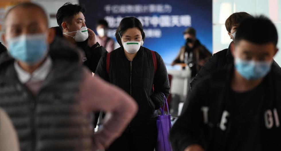 Imagen referencial. Los pasajeros usan mascarilla como medida preventiva contra el coronavirus cuando llegan de un vuelo en el Aeropuerto de Beijing. (AFP).